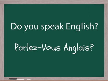 The words Do You Speak English and the French translation of Parlez-Vous Anglais written on a blackboard in chalk with an eraser at the bottom of the board.
