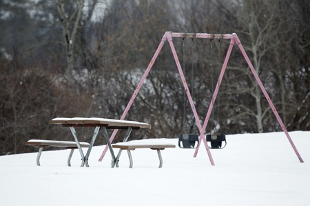 An old aged pink swingset and picnic table covered with snow at a park. photo
