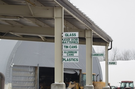 Signs at the recycling center directing where to put glass, lead acid batteries, aluminum cans, plastic, cardboard, tin cans, and paper. photo