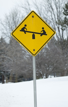 totter: A park or children at play sign showing kids on a teeter totter on a yellow and black sign against a snowy background. Stock Photo
