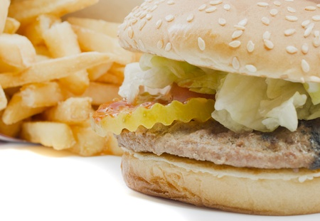 A burger with pickles, lettuce, tomatoes, mayonnaise, ketchup and more in close focus with a stack of fries in soft focus in the background. photo