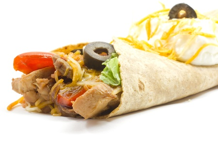 A beef and chicken fajita with red peppers, lettuce, cheese, black olives ans sour cream wrapped in a flour tortilla and served hot shot with close focus fading to soft in the background. photo