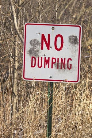 dumping: A red and white metal No Dumping sign with bullet holes in it against a canary grass background.