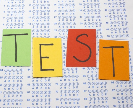 Colorful letters spell out the word Test on a bubble scantron test sheet ready to be filled out.