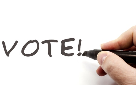 A hand with a black felt pen writing the word VOTE! making a great election concept. Stock Photo - 12701384