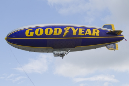 OSHKOSH, WI - JULY 27: The Good Year blimp Zeppelin, Spirit of Goodyear (with the distinctive yellow stripe), flies high over the 2012 AirVenture at EAA on July 27, 2012 in Oshkosh, Wisconsin.