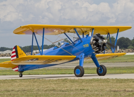 OSHKOSH, WI - JULY 27: A yellow and blue U.S. Army Bi-Plane heading down the runway for takeoff at the 2012 AirVenture at EAA on July 27, 2012 in Oshkosh, Wisconsin.