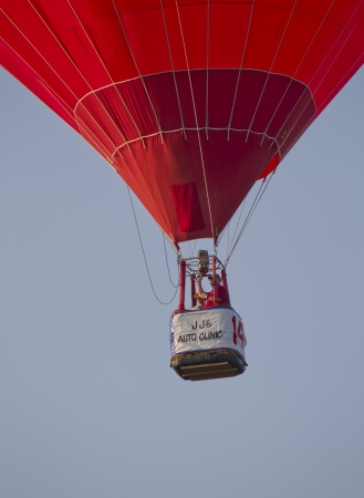SEYMOUR, WI - AUGUST 3: A close up of the basket of a red hot air balloon just after lift off at the Balloon Rally at the Annual Hamburger Festival on August 3, 2012 in Seymour, Wisconsin. Stock Photo - 14720532