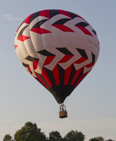 ascend: SEYMOUR, WI - AUGUST 3: A red, black, and white hot air balloon starts to ascend into the sky just above the trees at the Balloon Rally at the Annual Hamburger Festival on August 3, 2012 in Seymour, Wisconsin. Editorial