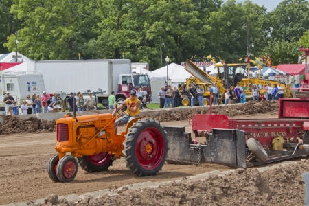 DE PERE, WI - AUGUST 18: A red & orange Minneapolis Moline tractor pulling the Tractor Tracks weight & competing at the Tractor Pull event at the Brown County Fair on August 18, 2012 in De Pere, Wisconsin.