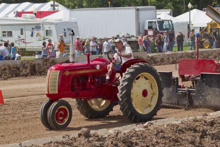 DE PERE, WI - AUGUST 18:  A red & yellow Cockshutt tractor pulling the Tractor Tracks weight & competing at the Tractor Pull event at the Brown County Fair on August 18, 2012 in De Pere, Wisconsin.