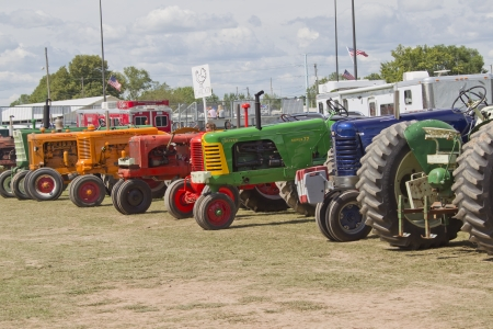 DE PERE, WI - AUGUST 18: A line of colorful vintage tractors lined up before competing at the Tractor Pull event at the Brown County Fair on August 18, 2012 in De Pere, Wisconsin.