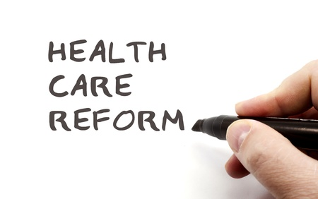 Hervorming van de gezondheidszorg in het zwart geschreven door een hand net klaar maken van een grote gezondheidszorg of ziekteverzekering concept.