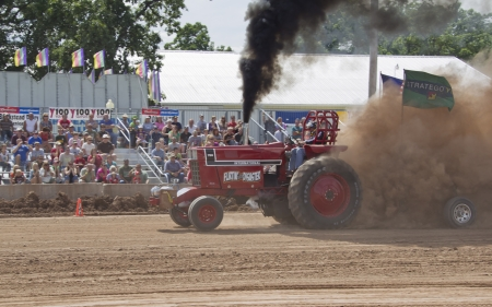 DE PERE, WI - AUGUST 18: A red International Tractor Flirtin with Disaster tractor pulling weights at the Tractor Pull event at the Brown County Fair on August 18, 2012 in De Pere, Wisconsin.