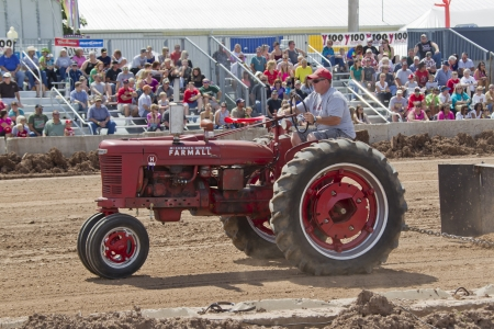 DE PERE, WI - AUGUST 18: A red McCormick Deering Farmall Tractor competing at the Tractor Pull event at the Brown County Fair on August 18, 2012 in De Pere, Wisconsin.