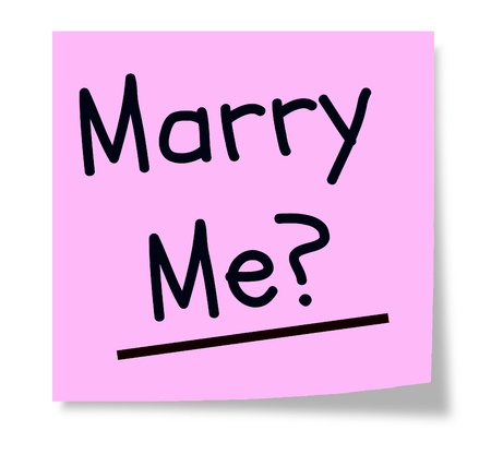 A pink square paper sticky note wth the words Marry Me? written in black making a great marriage concept. Imagens