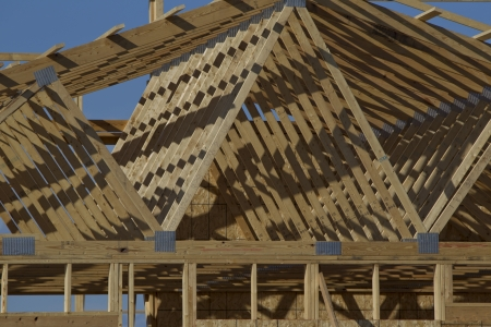 2x4 wood: A close up of wooden rafters on a building being constructed and in its framing process.