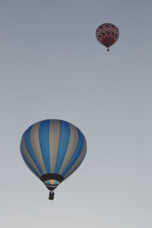 SEYMOUR, WI - AUGUST 3: A red and white balloon above a Silver and blue striped hot air balloon up in the sky at the Balloon Rally at the Annual Hamburger Festival on August 3, 2012 in Seymour, Wisconsin.
