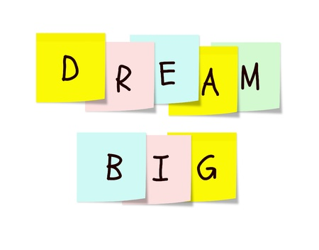 Colorful paper square sticky notes arranged with the words Dream Big on them making a great dreamer type concept.