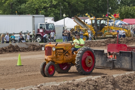 DE PERE, WI - AUGUST 18: A Minneapolis Orange & Red Tractor pulling the track weights at the Tractor Pull event at the Brown County Fair on August 18, 2012 in De Pere, Wisconsin.