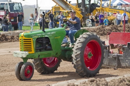 DE PERE, WI - AUGUST 18: A Oliver Super 77 Green & Red Tractor pulling the track weights at the Tractor Pull event at the Brown County Fair on August 18, 2012 in De Pere, Wisconsin.