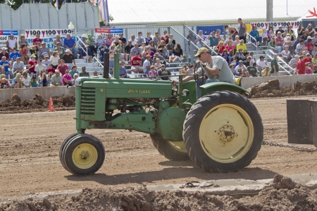 DE PERE, WI - AUGUST 18: A vintage John Deere A green & yellow Tractor competing at the Tractor Pull event at the Brown County Fair on August 18, 2012 in De Pere, Wisconsin.