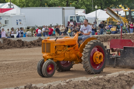 DE PERE, WI - AUGUST 18: A vintage Minneapolis Moline ZB orange & red Tractor pulling the weight tracks at the Tractor Pull event at the Brown County Fair on August 18, 2012 in De Pere, Wisconsin.