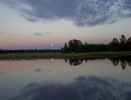 Blue Moon in Stormy dark cloudy skies over a lake as it is getting dark with a reflection in the water  photo