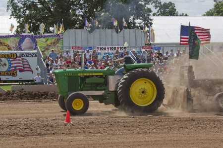 DE PERE, WI - AUGUST 18: Close up of John Deere 6030 Tractor competing at the Tractor Pull event at the Brown County Fair on August 18, 2012 in De Pere, Wisconsin.