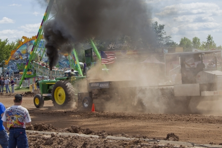 DE PERE, WI - AUGUST 18: John Deere 6030 Tractor end of pull with black smoke at the Tractor Pull event at the Brown County Fair on August 18, 2012 in De Pere, Wisconsin.