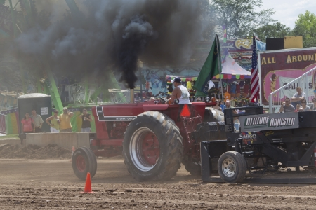 DE PERE, WI - AUGUST 18: Red International 966 Tractor ending the run in black smoke at the Tractor Pull event at the Brown County Fair on August 18, 2012 in De Pere, Wisconsin.