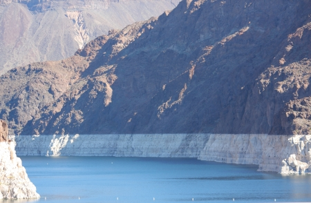 Lake and Water below Hoover Dam shows white ring mark showing low water levels. photo