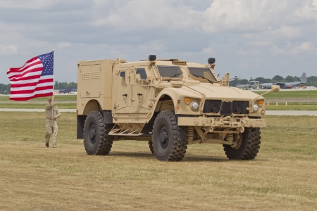 OSHKOSH, WI - JULY 27: A Soldier, American Flag, & Humvee on parade during Veterans Day events at the 2012 AirVenture at EAA on July 27, 2012 in Oshkosh, Wisconsin.