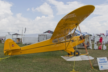 OSHKOSH, WI - JULY 27: Yellow Piper Cub Plane ready for Alaska on display with snowshoe and furs at the 2012 AirVenture at EAA on July 27, 2012 in Oshkosh, Wisconsin.