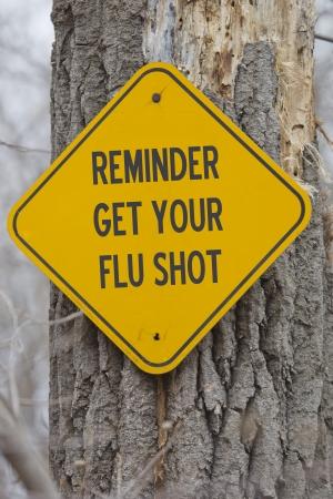 gripe: Recordatorio Get Your Sign vacuna contra la gripe en un árbol haciendo un gran disparo concepto gripe.