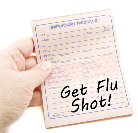 flu shot: Important Message Get Flu Shot written on pink paper with a hand holding it. Stock Photo