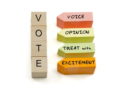 opinions: VOTE spelled out on blocks with paper with the words Voice Opinion Treat with Excitement.