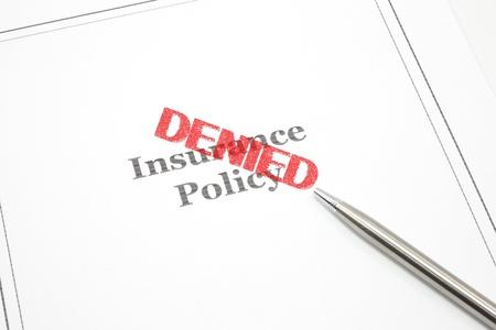 Une police d'assurance et une plume et la parole refusé de timbre rouge à travers la politique.