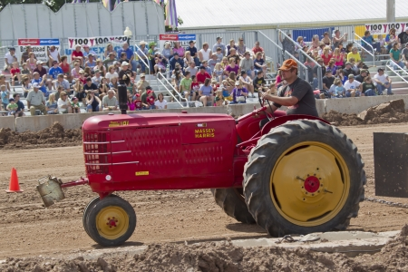 county side: DE PERE, WI - AUGUST 18: Side veiw of a red Massey Harris Tractor competing at the Tractor Pull event at the Brown County Fair on August 18, 2012 in De Pere, Wisconsin. Editorial