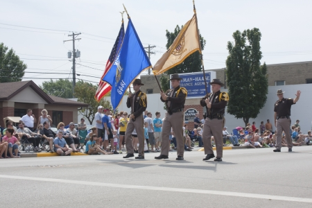sheriffs: SEYMOUR, WI - AUGUST 4:  Sheriffs Marching with Flags at the Annual Hamburger Festival Parade on August 4, 2012 in Seymour, Wisconsin.