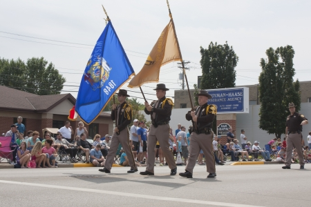 sheriffs: SEYMOUR, WI - AUGUST 4:  Close up of Sheriffs Marching with Flags at the Annual Hamburger Festival Parade on August 4, 2012 in Seymour, Wisconsin.