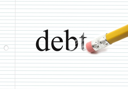 The word debt written on notebook paper with the end of a pencil erasing the black letters showing eraser marks making a great concept.