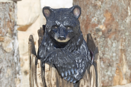 Black Bear Cub peaking out of Stump wood carving created with chainsaw and painted.