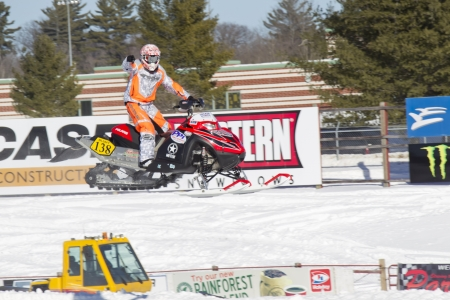 polaris: EAGLE RIVER, WI - MARCH 2:  Red and Black Polaris Snowmobile Racer Pointing to crowd during a race on March 2, 2013 in Eagle River, Wisconsin. Editorial