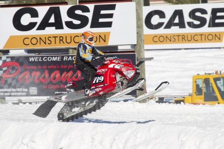 polaris: EAGLE RIVER, WI - MARCH 2:  Red and Black Polaris Snowmobile crashing down during a race on March 2, 2013 in Eagle River, Wisconsin.