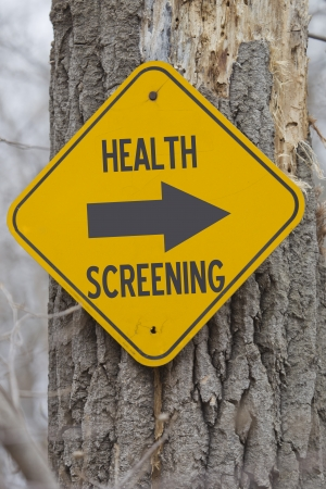 screening: A yellow sign on a tree showing which way for Health Screening making a great employer health screening concept. Stock Photo