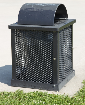 A metal Square Green Garbage or refuse can in a park Stock Photo