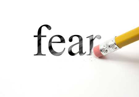 erase: The word Fear written with a pencil on white paper.  An eraser from a pencil is starting to erase the word fear.