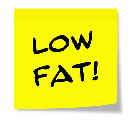 Low Fat written on a paper square Yellow Sticky Note making a great diet concept.