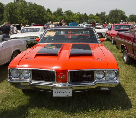 cutlass: IOLA, WI - JULY 13:  1972 Red with black stripes Olds Cutlass Car at Iola 41st Annual Car Show July 13, 2013 in Iola, Wisconsin.